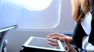 Woman using digital tablet on airplane video