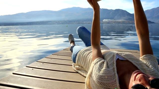 Woman using digital tablet on wooden dock video