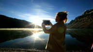Woman using digital tablet to photograph lake video