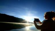 Woman using digital tablet to photograph lake video
