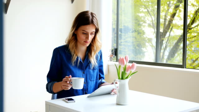 Woman using digital tablet while having coffee 4k video