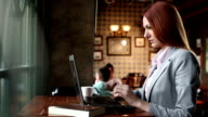 Woman using her laptop in a coffee shop video