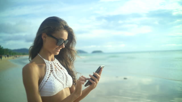 Woman Using Her Mobile Phone.On The Beach video