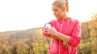 Woman using her smart phone while jogging in nature video