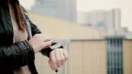 Woman using her smartwatch touchscreen standing on the roof, then walks away. hands closeup. FullHD video