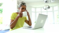Woman Using Laptop And Talking On Phone In Kitchen At Home video