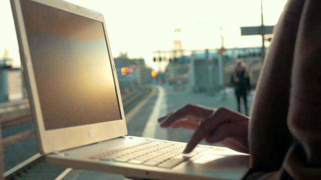 Woman using laptop at the station platform video