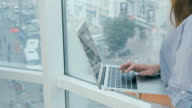 Woman using laptop computer near the panoramic window in modern bright office video