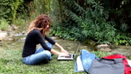 Woman using laptop in park video