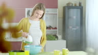 Woman using mixer in kitchen video