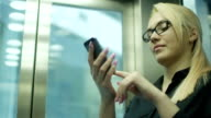 Woman Using Mobile Phone and Smile in Office Elevator video