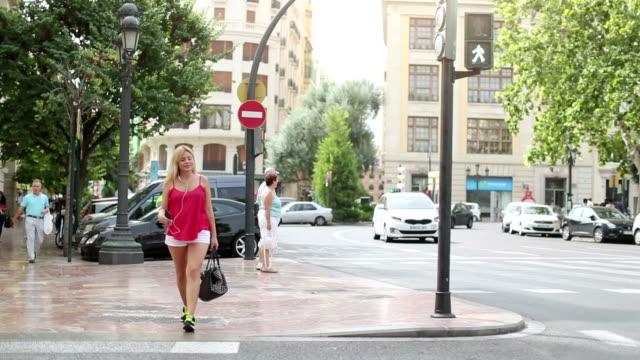 Woman using mobile phone in urban settings: crossing road video