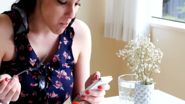 Woman using mobile phone while having meal 4k video