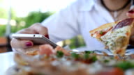Woman using mobile phone with eating pizza video