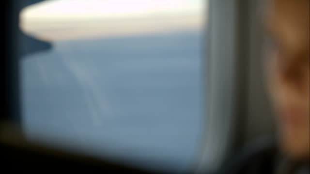 Woman using pad during flight and looking out the window video