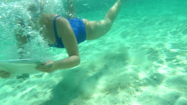 Woman using pad to make underwater shot video