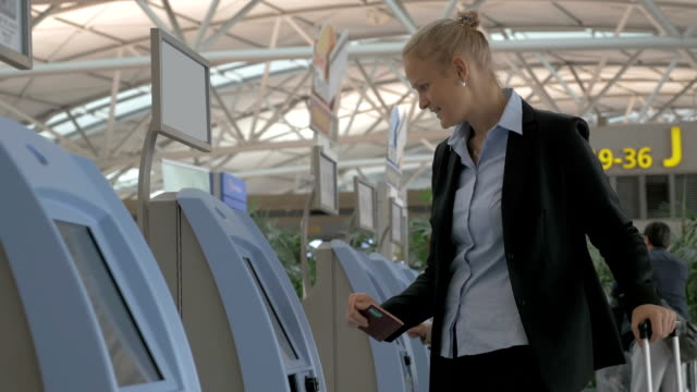 Woman using self check-in machine in the airport video