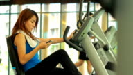 Woman using smart phone at gym video