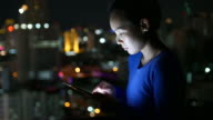 Woman using smart phone at night and Bokeh of City on Top roof of Hotel video