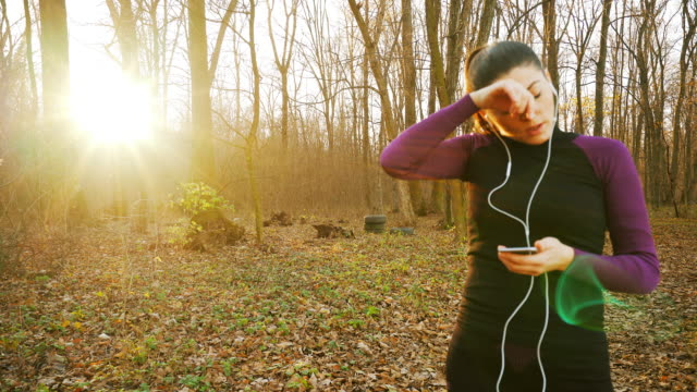 Woman using smart phone while jogging. video