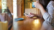 Woman using smartphone and take a coffee at coffee shop video