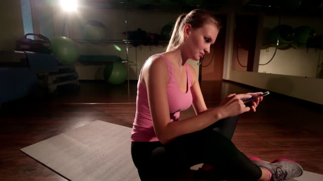 Woman using smartphone application to build custom routine in gym crane shot video