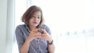 4K : Woman using smartphone in living room video