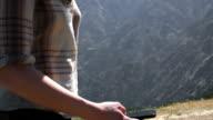 Woman using smartphone in mountain range video