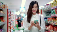 Woman using smartphone in supermarket,Slow motion video