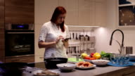 Woman using smartphone in the kitchen video