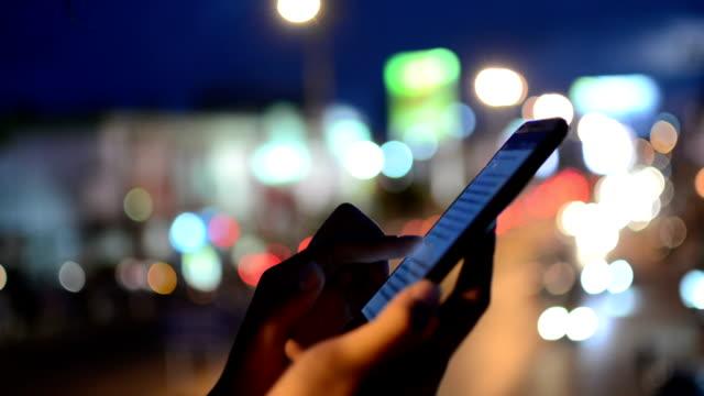 Woman using smartphone, night. video
