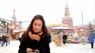 Woman using smartphone standing in the winter on the Red Square in Moscow, in front of Kremlin and St. Basil's Cathedral video