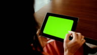 Woman Using Tablet  at the table. Green Screen video