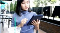 Woman using tablet in a coffee shop video