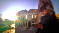 Woman using tablet in front of colosseum video