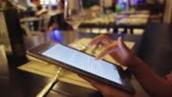 woman using tablet in restaurant night scene video