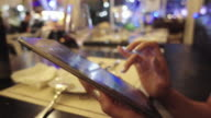 woman using tablet in restaurant video