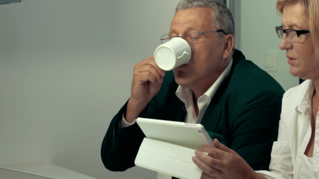 Woman using tablet, man drinking coffee video
