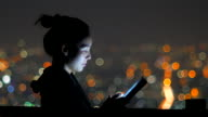 Woman using tablet pc at night with bokeh background video