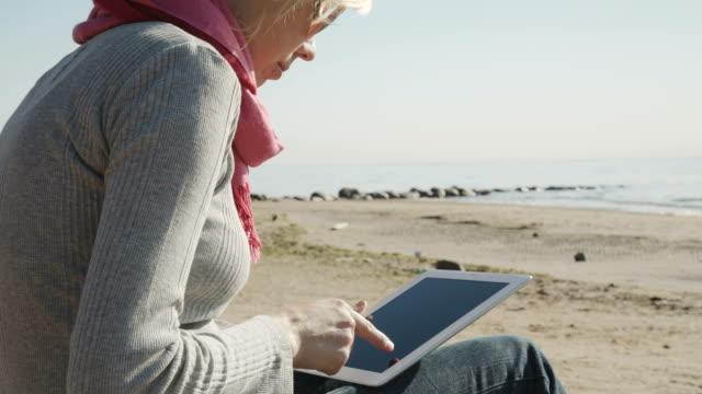 woman using  tablet pc on the beach video