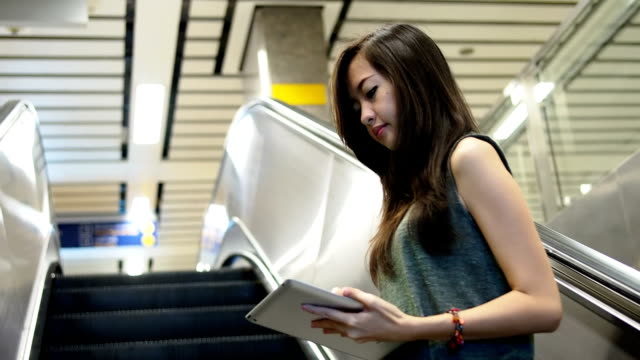 Woman using tablet while moving up on escalator video
