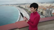 Woman using touch screen tablet in the mediterranean city video
