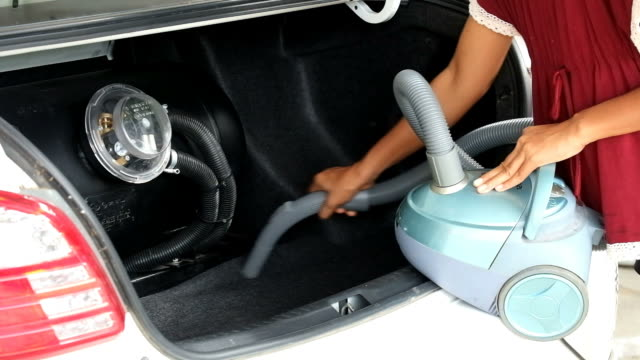 Woman vacuuming car trunk, clean dirty car trunk with handy vacuum video