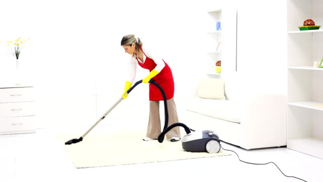 Woman vacuuming her living room. video