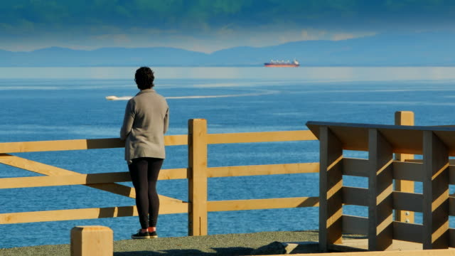 Woman Viewing Boat on Wide Ocean Sea, Olympic Mountains Background video