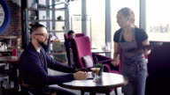 A woman waiter brought a cocktail on a tray for a stylish hipster, who has hair removed in a ponytail, a man browses fashion blogs on a laptop in a trendy restaurant video