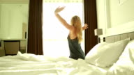 woman wakes up in hotel room, arms outstretched video