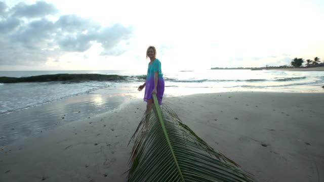 Woman walking along the beach. Dragging huge palm leaf. Holiday fun video