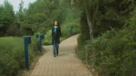 Woman walking along the pavement in park video
