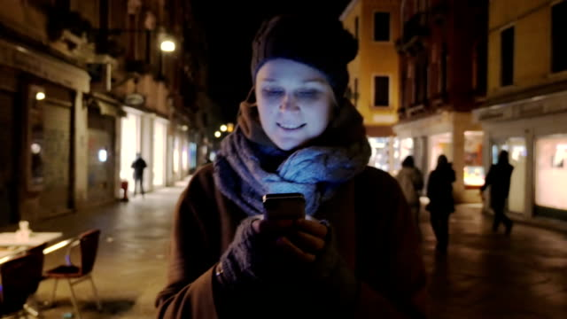 Woman walking at night and chatting on cell phone video